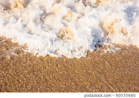 sea waves splash foam on the sunny beach 60535660