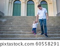 father and daughter walking down the stairs and holding hands 60558291