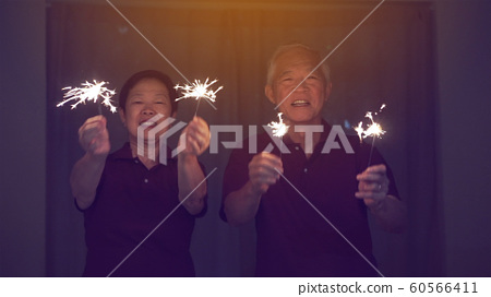 Asian senior couple playing firework, sparklers, fire cracker at night. Concept celebrating life 60566411