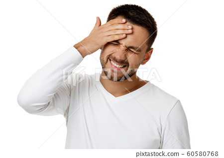 upset bearded man in casual white shirt keeps hand on head 60580768