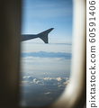 View from cabin of airplane.Through the window. Plane photography above clouds and mountains. 60591406