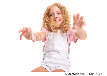 blond baby sits on a chair and pulls hands on a white studio background 60593749