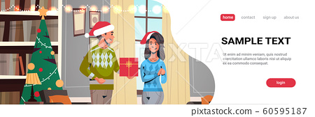man in santa hat giving gift present box to woman young couple celebrating merry christmas happy new year winter holidays concept modern living room interior copy space portrait horizontal 60595187