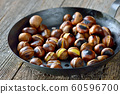 Roasted chestnuts with a perforated chestnut pan on an old wooden table  60596700