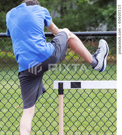 Runner perfoming hurdle fence drill 60600515
