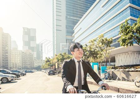 Businessman riding bicycle to work on urban street 60616627