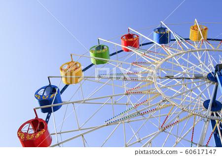 Underside view of a ferris wheel over blue sky 60617147