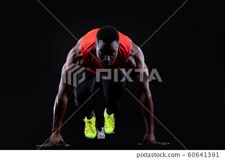 Male runner on starting blocks 60641391