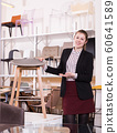 Saleswoman offering bar stools in furniture store 60641589