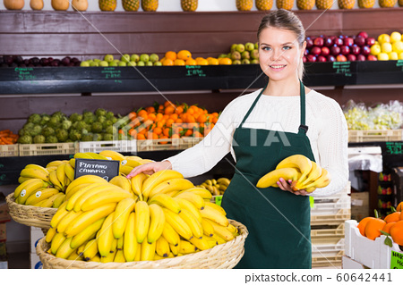 Young female in apron selling fresh bananas on the market 60642441