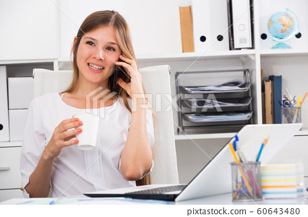 Business woman with phone relaxing at workplace 60643480