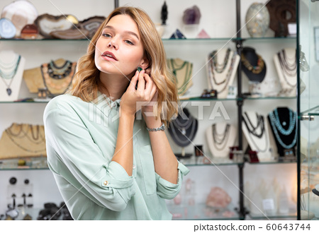 Woman choosing natural nephrite earrings 60643744