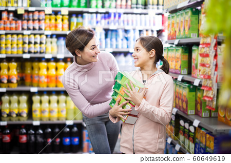 mature woman with daughter choosing refreshing beverages in supermarket 60649619