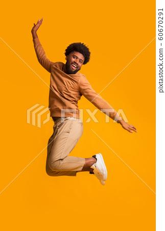 Positive afro guy jumping up over orange background 60670291