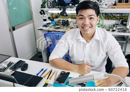 Man working at smartphone repair shop 60722418
