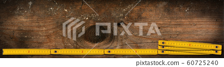 Yellow wooden folding ruler on a work table with copy space 60725240
