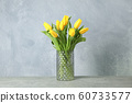 Beautiful yellow tulips in a glass vase on gray 60733577