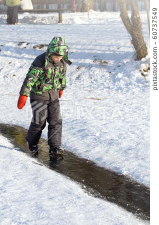Boy Sliding on Ice Rink 60737549