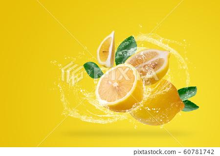 Water Splashing and yellow lemon fruit on a yellow 60781742