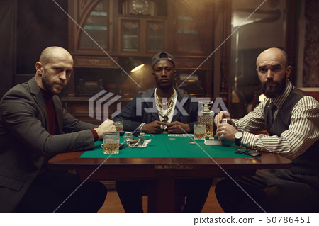 Poker players with cards playing in casino 60786451