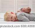 Smiling blond boy and little newborn sister 60814068