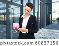 Caucasian woman in office clothes holds a pink pig moneybox and waits a coleague near the office 60837150