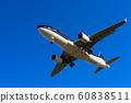 Airplane fly overhead against blue sky 60838511