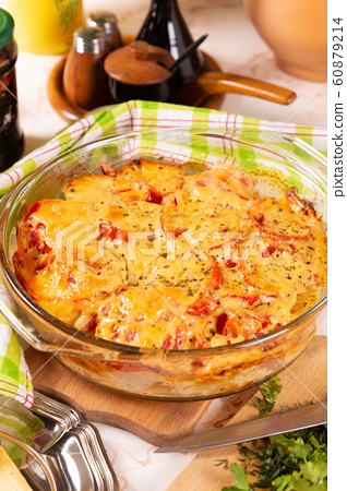 Potatoes baked with tomatoes and sweet peppers 60879214