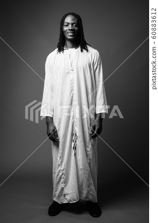 Young handsome African man wearing traditional clothes in black 60883612