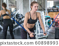 sporty woman doing exercise with fitness trx straps to strengthen his abdominal muscle in gym. 60898993