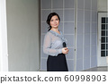 Portrait of a beautiful fashionable Asian woman in a business suit with a microphone 60998903