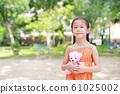 Portrait of happy little Asian child in green 61025002