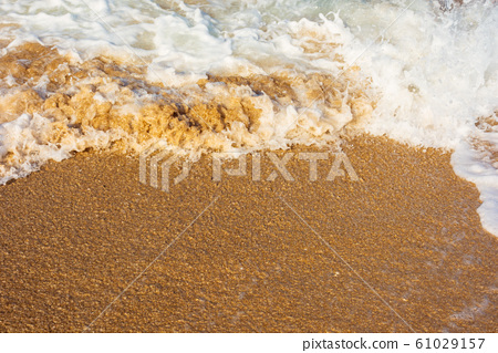 sea waves splash foam on the sunny beach 61029157