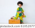 Portrait of young African boy stand with one leg on wood box express question emotion 61052077