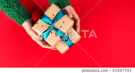 Gift box with green ribbon in female hands on red 61067393