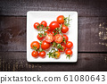 fresh tomatoes on white plate with wooden dark 61080643