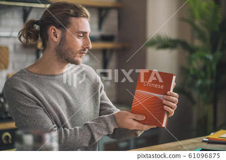 Young handsome man studying Chinese at home 61096875