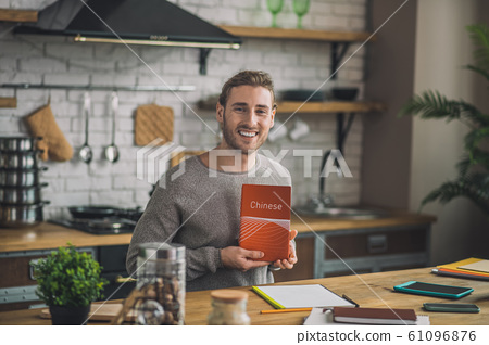 Young handsome man holding Chinese grammar book 61096876