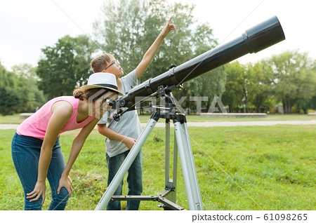 Children teenagers in the park looking through a telescope 61098265