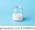 Large white crystals of sea salt in a glass bottle on a pastel blue background. 61098656