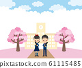 A graduate standing in front of a cherry blossoming school 61115485