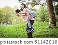 Happy asian father laugh giving piggyback ride to beautiful daughter having fun,hug together,smiling child girl enjoying active game with dad, young man carrying cute daughter on back,playing in outdo 61142010