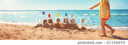 boy building a sandcastle at the beach in summer 61146859