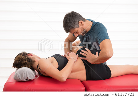 Osteopath working on a lumbar roll 61157723