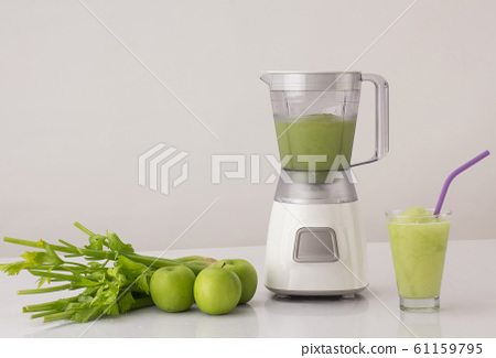 blender with celery and apples on the kitchen table 61159795