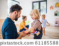 Young family with two small children indoors in bedroom playing. 61185588