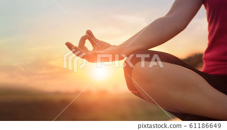 Woman yoga practicing and meditating by the lake in summer 61186649