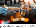 Close-up of two men clinking glasses of whiskey drink alcohol beverage together at bar counter in the pub after work on colorful background 61186651