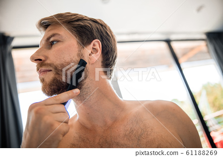Handsome young man brushing his beard in bathroom 61188269