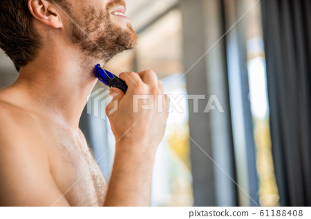 Smiling young man removing stubble from neck 61188408